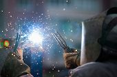 foto of protective eyewear  - Heavy industry welder worker in protective mask hand holding arc welding torch working on metal construction - JPG