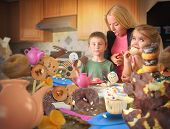 stock photo of obese children  - Two children are eating messy junk food snacks such as cookies donuts and cupcakes in the kitchen with an angry mother - JPG