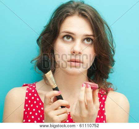 Beautiful Girl With A Brush And Blusher On A Blue Background In Soft Focus