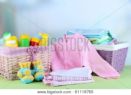 Pile of baby clothes  in basket, on table on color background