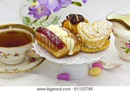 Afternoon tea with cakes and antique tea cup.