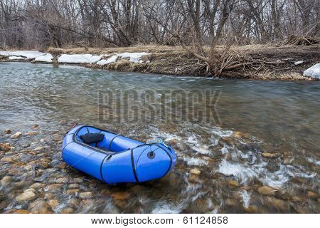 a packraft (one-person light raft used for expedition or adventure racing) on a shallow river - Cache la Poudre River, Fort Collins, Colorado, winter or early spring scenery