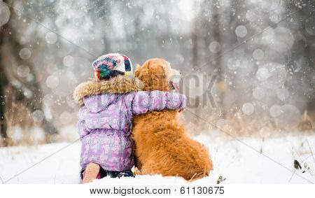 little girl hugging dog and looks forward