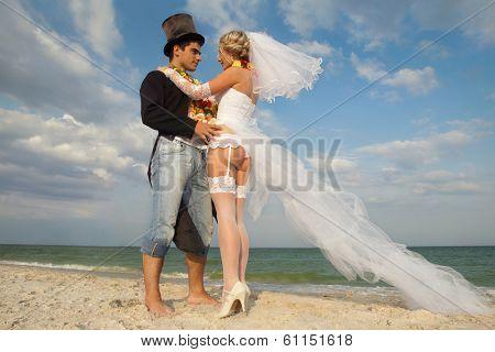 Groom with bride wearing lei on beach