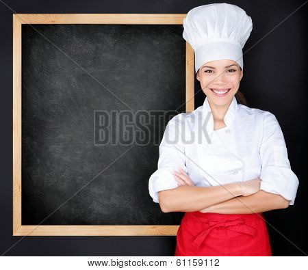 Chef showing menu blackboard. Woman in front of blank menu blackboard. Happy female chef, cook or baker by empty chalkboard menu display wearing chef whites uniform and hat