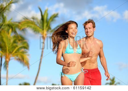 Couple having fun on beach vacation travel laughing happy running together playful and joyful. Woman in bikini and man in swimwear. Beautiful interracial lovers in love on honeymoon on Hawaii.