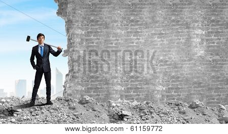 Young determined businessman breaking wall with hammer