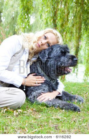 Young blond woman with her dog in the park