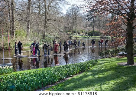 Lisse, Netherlands - April 20, 2013: Tourists walking on water in Keukenhof park, also known as the Garden of Europe, is the world's largest flower garden.