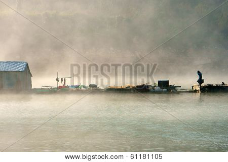 House On Lake In Foggy Morning