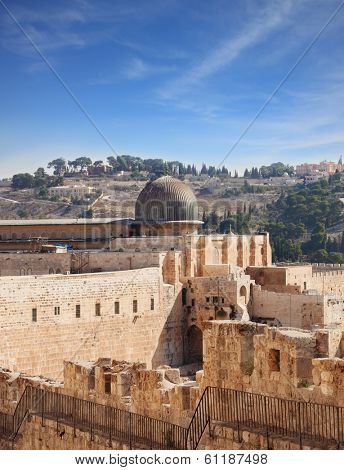 The ancient walls of Jerusalem, lit morning sun. The dome of the Al Aqsa Mosque on the Temple Mount in Jerusalem