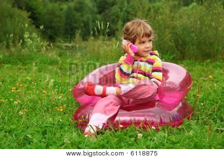 Little Girl Sits Talks By Toy Phone In Inflatable Armchair