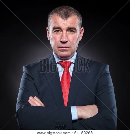 serious mature business man looking at the camera with hands folded on black background