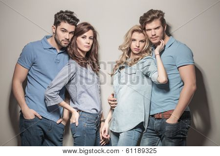 relaxed casual group of young fashion friends standing together against gray studio wall