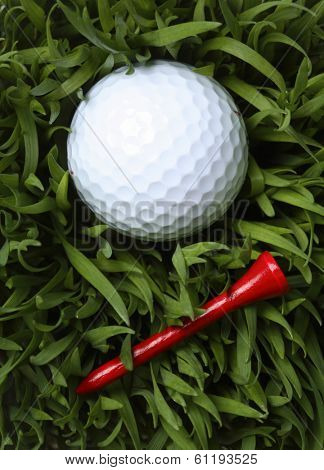 Golf ball with red tee on green grass
