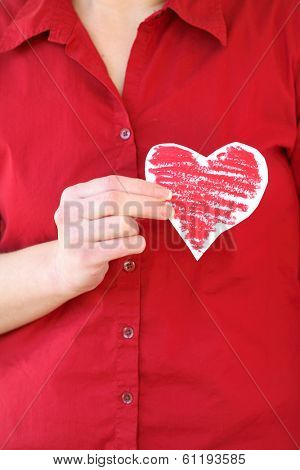 Woman with red shirt holding red colored paper heart