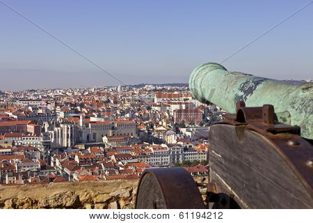 Lisbon, Portugal - February 01, 2013: Sao Jorge (St. George) Castle in Lisbon, Portugal. Old Bronze cannon and a view of Lisbon's Baixa (downtown) District and river.