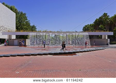 Lisbon, Portugal - August 02, 2013: Visitors pass in front of the Waterfall of the Jardins Dagua (Water Gardens) in the Parque das Nacoes (Park of Nations).