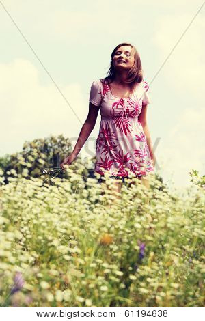 Smile teen open hands standing on field ful of flowers