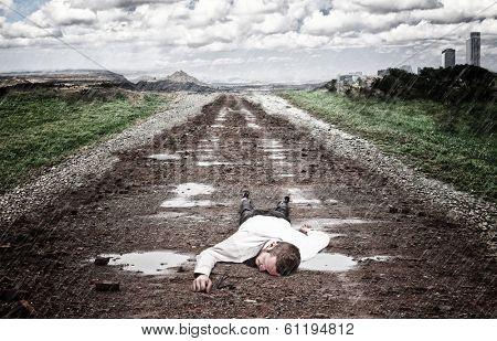 stressed man lying on ground with rain