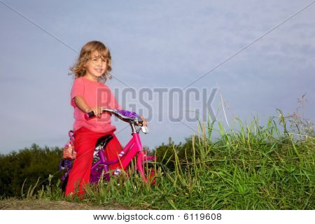Young Curly Girl Biker Rests In The Field