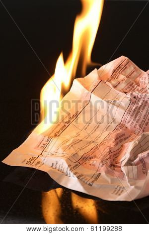 Tax forms on fire with black background