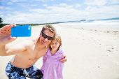 picture of selfie  - Smiling father taking selfie photograph with young daughter at beach using mobile phone - JPG