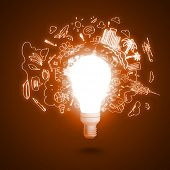 Conceptual image of electric bulb against orange background