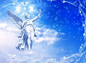 stock photo of archangel  - a statue of angel over winter sky with snow flakes - JPG