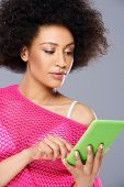 Sexy African American woman in a fashionable trendy pink blouse with a tablet in her hands on a grey