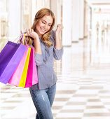 Woman having fun in shopping center, smiling girl with closed eyes holding in hands colorful paper b