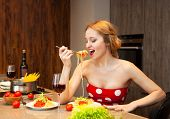stock photo of spaghetti  - Sexy young blond woman eating spaghetti in the kitchen at home - JPG