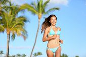 Bikini woman running on beach smiling happy and on tropical summer beach with palm trees. Beautiful