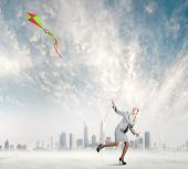 Young happy businesswoman running with colorful kite