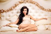 image of legs apart  - Beautiful and attractive young adult female brunette sensuality woman posing on bed in exclusive apartment - JPG