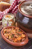 stock photo of stew pot  - Traditional goulash or pork stew in red crock pot - JPG