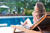 Happy young woman in bikini laying on chaise-longue luxury pool side