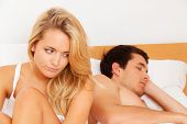 stock photo of adultery  - a young couple in bed has problems and crisis - JPG