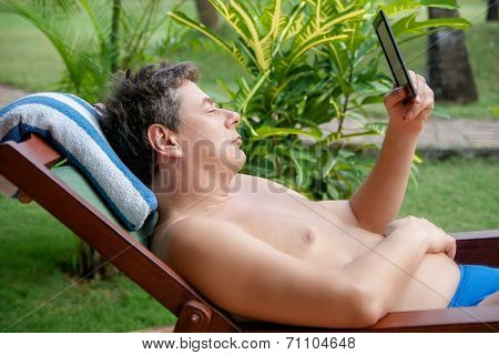 Man In A Deck-chair Is Reading In An  E-book-reader