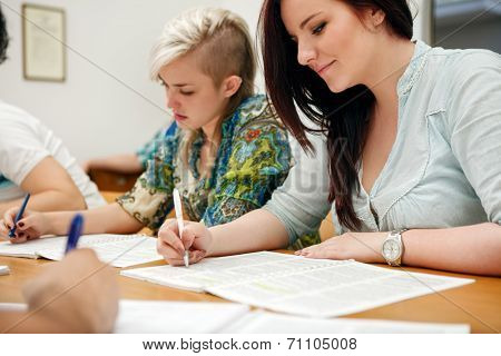 group of students sitting in classroom and writing