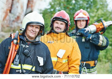 firefighter crew in uniform in front of fire engine machine and fireman team