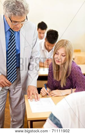 Teacher observes his  students class as they are taking a test.