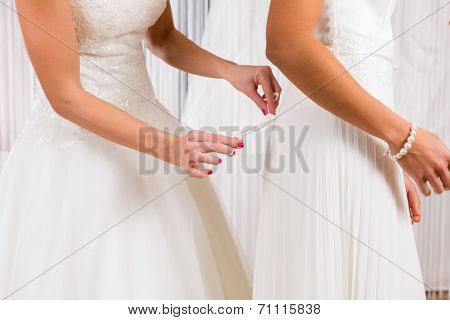 Women trying on together bridal gown in wedding fashion store
