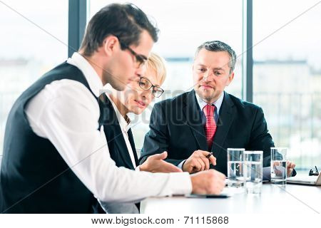 Business - meeting in office, the businesspeople are discussing a document on Laptop computer and working as team