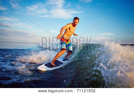 Young man surfboarding on summer vacation