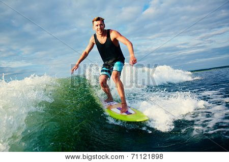 Male surfer riding on waves