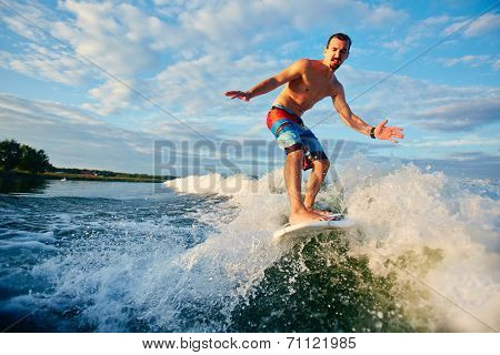 Adventurous man surfboarding in the sea
