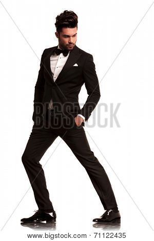 side view of a fashion man in tuxedo with hands in pokets looking to his side on white background