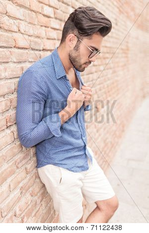 casual man pulling his colar and looks down , against brick wall