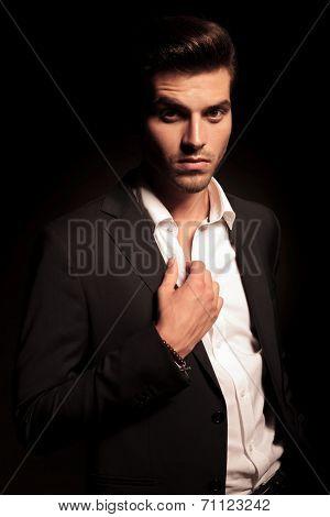 elegant man holding his collar on black background
